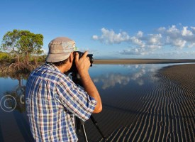 Image of photographer taking a photo on beach, Port Douglas, North Queensland, Australia